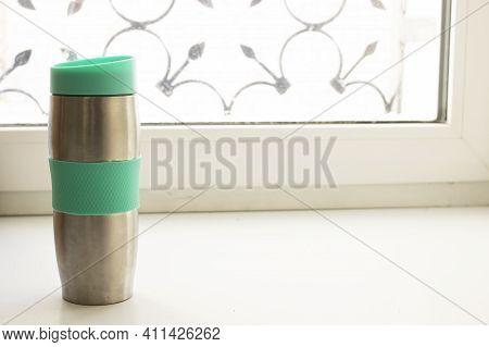 Metal Thermo Mug On Windowsill In Sunlight