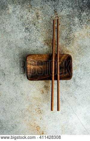 Asian Food Place Setting With Chopsticks On Stone Background