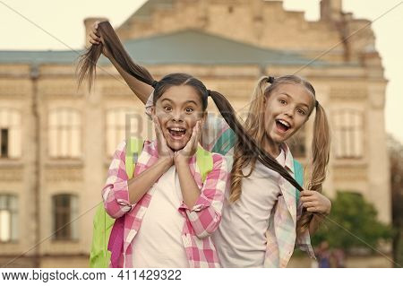 Keep Your Hair Long. Happy Children Hold Long Hair. School Girls In Pigtails. Trendy Long Hairstyle.