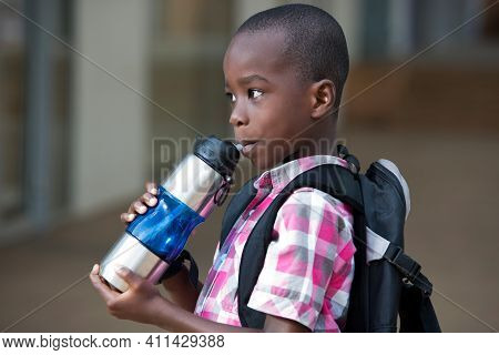 Small Schoolboy With A Backpack, Standing Drinks Water In A Bottle On The Way Down The Class.