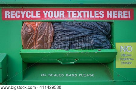 An Overflowing Textile Recycling Container Or Bin