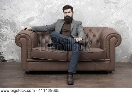 Rent Apartment. Bearded Man With Confident Face Sit Leather Couch. Loft Interior Apartment. Business