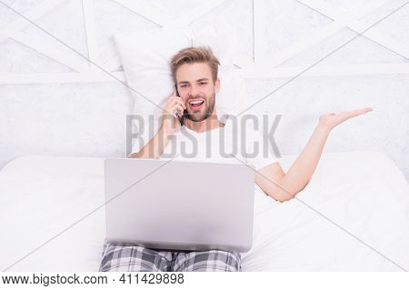 Handsome Man Talk On Phone Watching Video Conference Online By Laptop Computer In Bed, Informal Nego