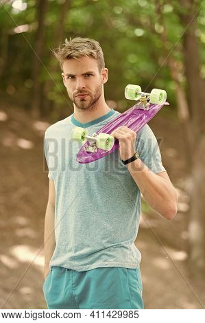 Penny Board Is His Travel Companion. Handsome Guy Hold Penny Board Outdoors. Athletic Skater With Pi