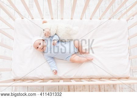 Baby In Crib With Teddy Bear Toy Goes To Bed Or Woke Up In The Morning, Family And Birth Concept