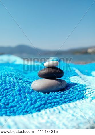Stack Of Pebble Stones On A Blue Beach Towel On A Sunny Day. Have Fun And Relax On The Beach. Travel