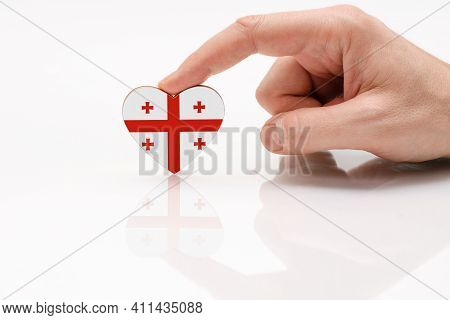 Flag Of Georgia. Love And Respect Georgia. A Man's Hand Holds A Heart In The Shape Of The Georgia Fl