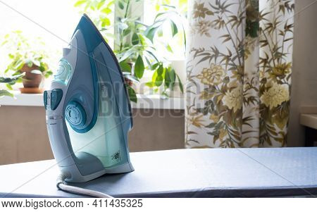 Iron On An Ironing Board In A Real Home Setting. Blue Iron