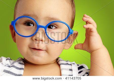Portrait Of Baby Boy Wearing Blue Eye wear against a green background