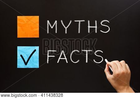 Hand Writing Myths Or Facts Concept With White Chalk On Blackboard. Choose The Facts Over The Myths.