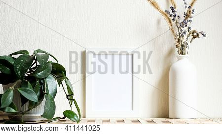 Poster With Copy Space. Mockup Of A Wooden Frame With Home Plant Liana With Vase With Dried Flowers.
