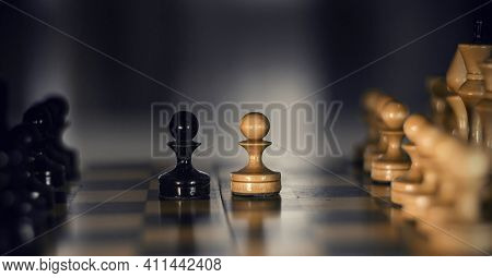 Two Pieces On The Chessboard Are Pawns: Black And White. Wooden Chess Pieces On The Chessboard. Inte