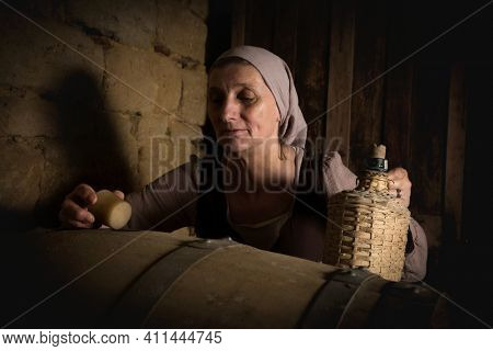 Woman in medieval peasant outfit checking wine barrels in the cellar  of a property released authentic medieval castle in France