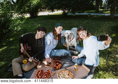 Company Of Beautiful Young People And Dog Having An Outdoor Lunch.