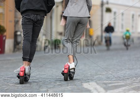 Rear View Of Unrecognizable Trendy Fashinable Teenagers Riding Public Rental Electric Scooters In Ur