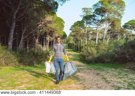 Garbage Collection In Forest. Volunteer Man With Garbage Bag Cleaning-up The Forest From Plastic Pol