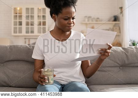 Depressed Sad Black Girl Holding Last Cash Money And Papers Calculate Domestic Bills At Home. Africa