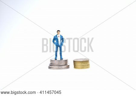 Selective Focus Image Of Miniature Rich People Standing On Coin Money. Business And Economy Concept
