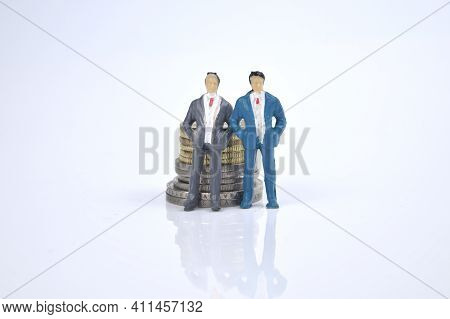 Selective Focus Image Of Business Person Miniature With Stack Of Coins On A White Background. Life C
