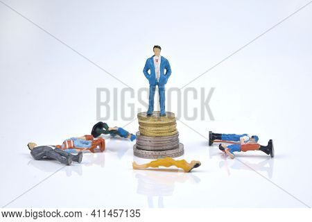 Selective Focus Image Of Rich People Miniature Standing On Stack Of Coins With Peoples Fall Down Sur