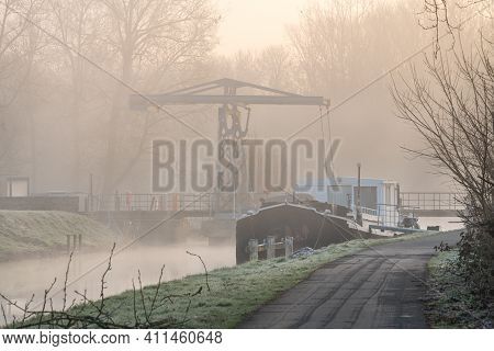 On A Foggy Cold Morning Along The River With A Double Beam Drawbridge And Behind The Full Moon
