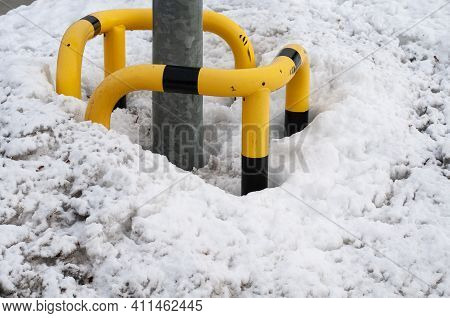 The Post Of A Street Light With A Black And Yellow Boundary With A Heap Of Dirty Snow In Winter