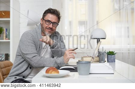 Happy older man working online with laptop computer at home sitting at desk. Home office, browsing internet, study room. Portrait of mature age, middle age, mid adult man in 50s.