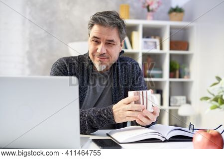Bearded businessman working online with laptop computer at home sitting at desk. Home office, browsing internet, study room. Portrait of mature age, middle age, mid adult man in 50s.