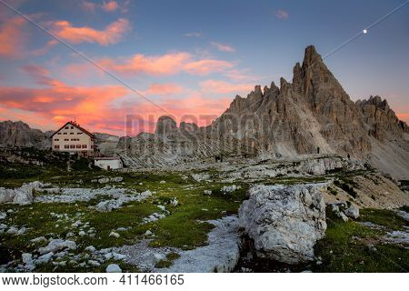 Mountain valley with beautiful house  at sunset time. Landscape with real moon, high rocks, colorful sky, clouds, sunlight. Mountains in Tre Cime park in Dolomites, Italy. Italian alps