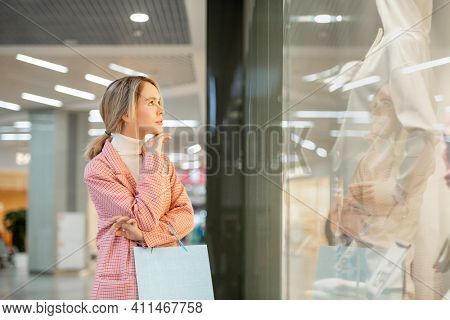 Young woman standing in front of the shopping window and looking at mannequin during her shopping in the mall