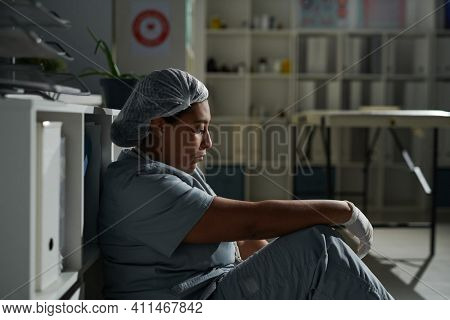 Side view of young tired mixed-race female clinician in uniform sitting on the floor while relaxing after hard working day in modern clinics