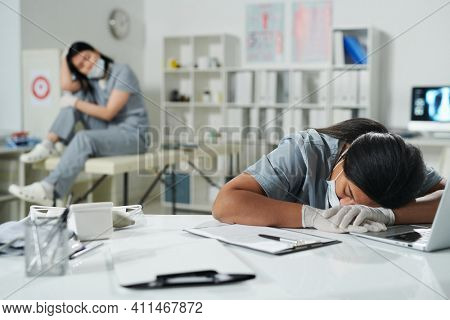 Young tired mixed-race female clinician in uniform and protective workwear napping in front of camera while keeping her head on desk