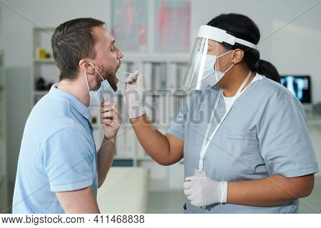 Contemporary mixed-race female clinician using coronavirus test cotton bud for oral swab of young man sitting in front of her with open mouth