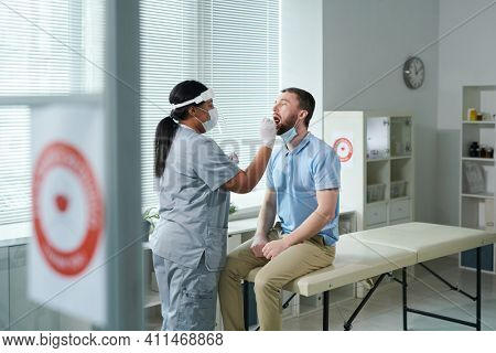 Young male patient with open mouth sitting in front of female clinician in protective workwear and being tested for covid with oral swab in clinics