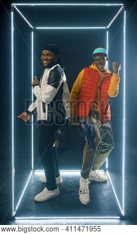 Two stylish rappers poses in glowing cube