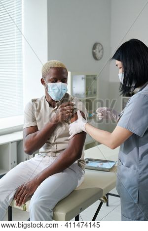 Young clinician of Asian ethnicity in uniform and protective mask vaccinating African guy sitting in medical office of clinics