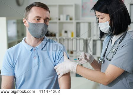Female clinician or nurse of Asian ethnicity in uniform and protective mask vaccinating young man sitting in medical office of modern clinics