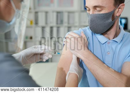 Young man holding sleeve of his shirt while nurse in protective workwear making him injection during vaccination against covid in clinics