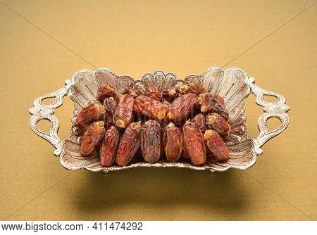 Dates- a staple food in Ramadan. Finest quality arabian dates in a silverware. An ornamental tray full of Mabroom dates.