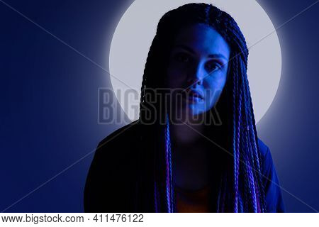 Portrait Of A Young Woman With Long Hair In Dark With Halo Around Her Head