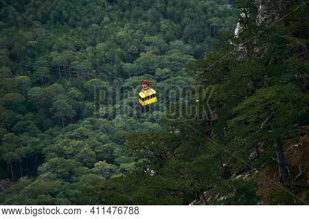 Cabin Of The Aerial Tramway Moves Between Wooded Mountain Slopes