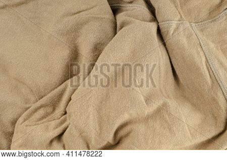 Crumpled Brown Fabric Background. A Wrinkled Brown Shirt With An Overdue Seam.