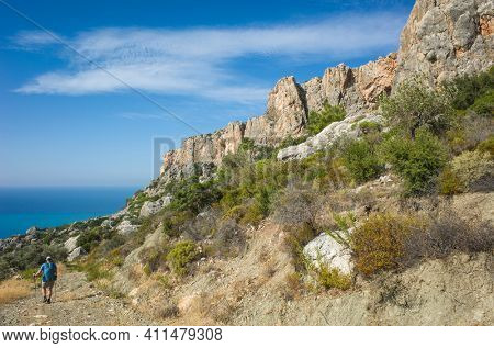Hiking Lycian way. Man is trekking on dry stony path along rocky mountain ridge on Mediterranean coast, Outdoor activity in Turkey. (stretch from Patara to Kalkan)