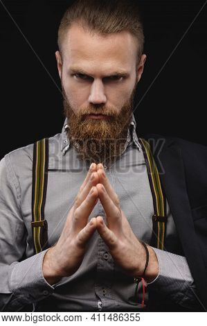 Portrait Of An Attractive Caucasian Bearded Man With A Stylish Hairstyle In A Shirt With Suspenders