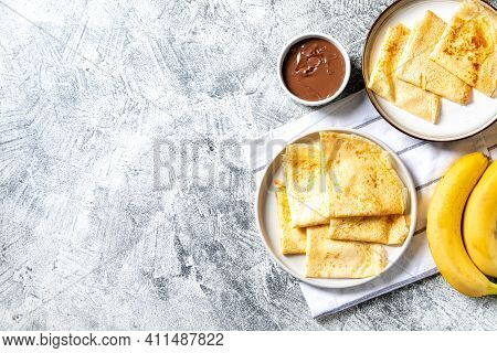Crepes, Thin Pancakes On A Plate. Chocolate Hazelnut Spread And Banana Filled Crepes On Plate. Tasty