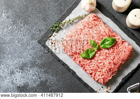 Mince. Fresh Raw Minced Meat On Paper And Black Slate Cutting Board, On Gray Background.