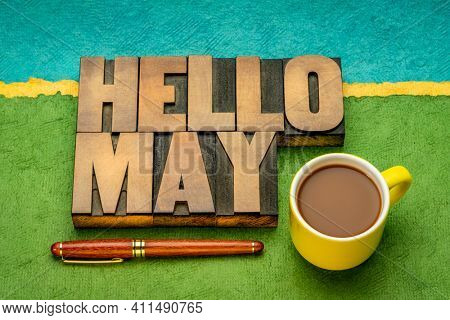 Hello May word abstract in vintage letterpress wood type with a cup of coffee against abstrax tpaper landscape, cheerful greetings