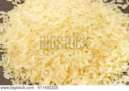Pile Of Raw Medium-grained Parboiled Rice On A Brown Dish, Close-up In Selective Focus