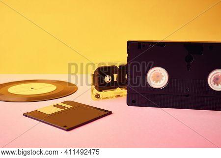 Vinyl Disc, Floppy Diskette, Vhs And Tape Cassete On Yellow Background. Vintage, Retro And Nostalgia