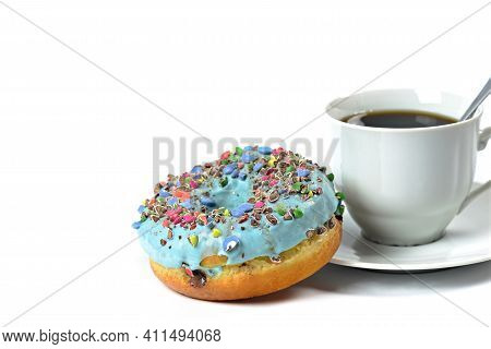 View Of A Sweet Donut With Blue Icing And Crushed Candies. Donut On A White Background With A Cup Of
